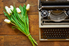 Le bouquet des tulipes blanches et la machine à écrire sur le backgound en bois complètent v Photos libres de droits