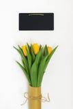 Le bouquet des tulipes jaunes a emballé en papier d'emballage dans le rétro style Photographie stock