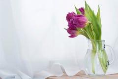 Le bouquet des tulipes roses dans un décanteur en verre sur une table en bois image libre de droits