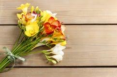 Le bouquet du freesia coloré fleurit sur le bois brun Photos stock