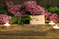 Le bouquet du lilas, bougie et vous remercient de carder sur le vieux backgr en bois Photos libres de droits