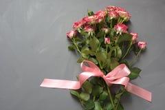 Le bouquet du rose a repéré des roses de buisson avec le ruban rose sur le fond gris Vue supérieure Carte romantique avec amour Photo stock