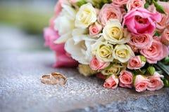 le bouquet du ` s de jeune mariée des roses et des anneaux de mariage Photographie stock libre de droits