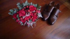 Le bouquet du ` s de jeune mariée des roses près des chaussures banque de vidéos