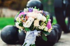 Le bouquet nuptiale de différentes fleurs a enveloppé le ruban de dentelle près du groupe de boulets de canon Photos libres de droits