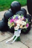 Le bouquet nuptiale de différentes fleurs a enveloppé le ruban de dentelle près du groupe de boulets de canon Images stock