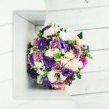 Le bouquet nuptiale de différentes fleurs a enveloppé le ruban de dentelle sur un fond blanc Images libres de droits