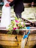 Le bouquet nuptiale est sur le bateau en bois à la pousse de mariage, une grande idée photos libres de droits