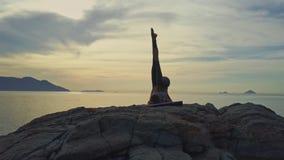 Le bourdon montre la silhouette de fille dans la pose de yoga contre le lever de soleil d'océan clips vidéos