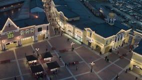 Le bourdon montre les bâtiments de magasin de achat avec l'illumination pleine des personnes de marche banque de vidéos