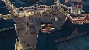 Le bourdon montre les dessus foncés de toit, bâtiments de magasin avec des personnes d'illumination et de marche banque de vidéos