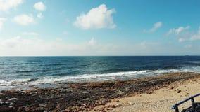 Le bourdon tiré des ressacs frappant la plage sablonneuse rocheuse polluée avec la construction en plastique de déchets et en mét banque de vidéos