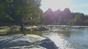 Le bourdon tourne autour de la fille faisant le yoga contre des rayons de Sun de rivière clips vidéos