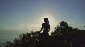 Le bourdon tourne autour de la silhouette de femme dans le padmasana sur la falaise banque de vidéos