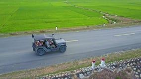 Le bourdon vole au-dessus de la jeep avec des touristes conduisant le long de la route clips vidéos