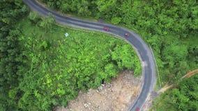 Le bourdon vole au-dessus de la route de courbe près de la montagne verte sur laquelle des conducteurs conduisant un atv de sport banque de vidéos