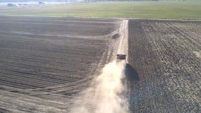 Le bourdon vole au-dessus du camion avec des pommes de terre soulevant des nuages de poussière banque de vidéos