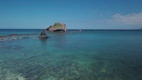 Le bourdon vole bas au-dessus de la surface de l'eau de la mer claire dans le jour d'été, de la côte à stupéfier l'île minuscule banque de vidéos