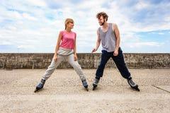 Le bout droit d'exercice de deux personnes extérieur fait du roller dessus Photo libre de droits