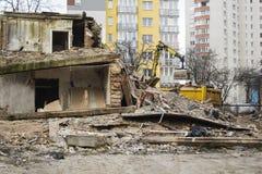 Le bouteur a démoli le vieux bâtiment sur le fond de nouveaux logements image stock