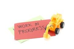 Le bouteur jaune de jouet sur le papier rouge et la tache floue expriment le travail en cours Photographie stock libre de droits