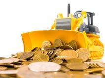 Le bouteur jaune a ratissé la pile des pièces de monnaie Images stock