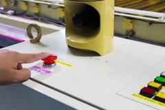 Le bouton d'arrêt d'urgence de pressing de main sur la machine automatique Image stock
