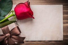 Le bouton de rose rouge a enveloppé la page de giftbox du papier blanche Image libre de droits