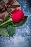 Le bouton de rose rouge a enveloppé le giftbox sur HOL métallique rayé de fond Photo stock