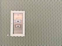Le bouton extérieur d'ascenseur de plan rapproché dedans à travers la flèche se connectent le fond texturisé par mur en acier ave Photographie stock libre de droits