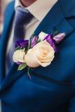 Le boutonniere du marié des roses crèmes Photo libre de droits
