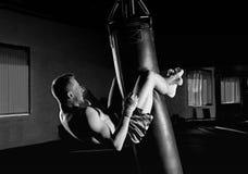 Le boxeur dans le gymnase accroché sur un sac de boxe et fait des torsions pour t photos libres de droits