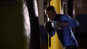 Le boxeur frappe le sac de sable L'homme de sports bat un sac de sable L'homme dans le gymnase L'entraîneur joue des sports Sac d banque de vidéos