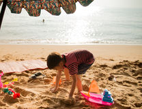 Le boy playing sand on the beach summer time Stock Photos