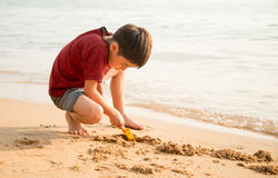 le boy playing sand on the beach summer time Stock Images