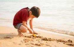 le boy que juega la arena en el tiempo de verano de la playa Imagenes de archivo