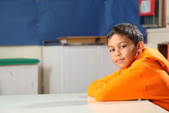 Le braccia dello scolaro 10 hanno piegato in profondità nell'aula di pensiero Fotografie Stock