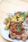 Le braciole di maiale con le mele ed il forno hanno arrostito le patate Fotografia Stock