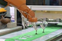 Le bras de robot pour le transfert la feuille en caoutchouc image stock