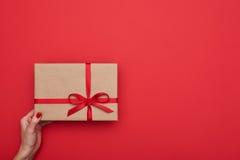 Le bras femelle tient le boîte-cadeau fait main dans le style de vintage Photo libre de droits