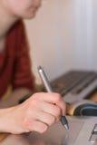 Le bras fonctionne la tablette de crayon lecteur Photo stock