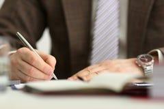 Le bras masculin dans le costume et le lien tiennent le stylo argent? photos libres de droits