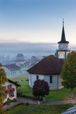 Le Brassus, Switzerland in a foggy winter morning. View of Le Brassus, a little village in the northern Switzerland, with a thick fog early in the morning in a Stock Photos