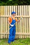 Le bricoleur dans l'uniforme fonctionnant bleu vérifie l'état du rouleau de peinture Images stock