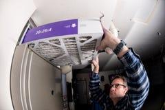 Le bricoleur remplace le filtre dans le four d'air chaud à une maison images stock