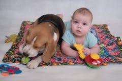 Le briquet et le bébé se trouvant sur le tapis Photos stock