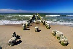 Le brise-lames en bois retraite dans la mer Image libre de droits