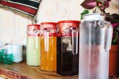 Le brocche di vetro con varietà di bevande della bacca e della frutta con i coperchi rossi stanno sulla tavola Fotografia Stock