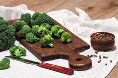 Le brocoli rapièce sur le conseil, le couteau et les épices de cuisine Photographie stock libre de droits