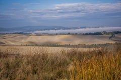 Le brouillard de début de la matinée forme une couche au-dessus des champs secs en Toscane Photo libre de droits